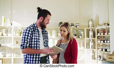 Young shop assistant with tablet serving an attractive woman...