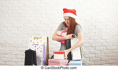 Young Shopaholic girl is picking up Christmas boxes.