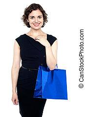 Young shopaholic woman carrying bright bag