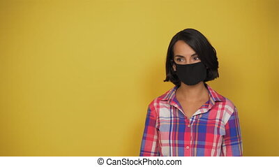 Young short-haired woman with dark hair on yellow background with black mask on her face looks carefully to side. Model in everyday clothes is worth it. Concept is virus, pandemic. Copy space.