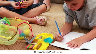 Young siblings doing arts and crafts on the rug at home in...