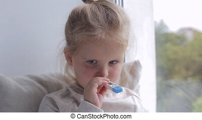 Young sick girl measures the temperature near window. Holding thermometer in her mouth