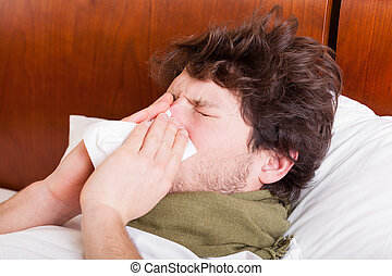 Young sick man blowing nose