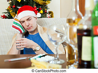Young sick man in red New Year hat - Sick man in red New...