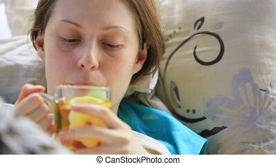 Young sick woman drinking tea.