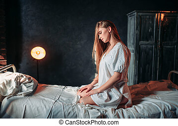 Young sick woman sitting on hospital bed