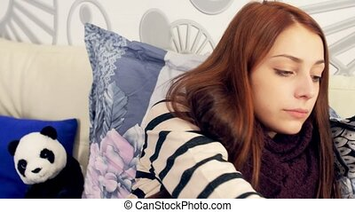 Young sick woman taking pills in her bedroom