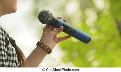 young singer singing into a microphone slow motion video