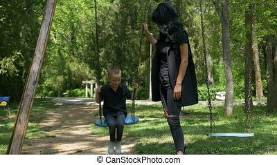 Young single mother pushing child on a swing set