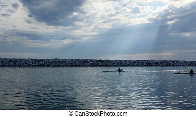 Young single scull rowing competitors paddle on the tranquil...