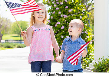 Young Sister and Brother Waving American Flags At The Park