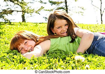 Young sisters - Portrait of happy girls playing on grass