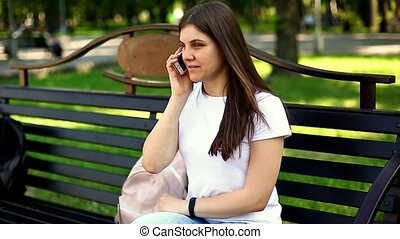 Young sitting on the bench calling ans speaking on mobile phone