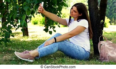 Young sitting on the grass and making selfie with a mobile phone