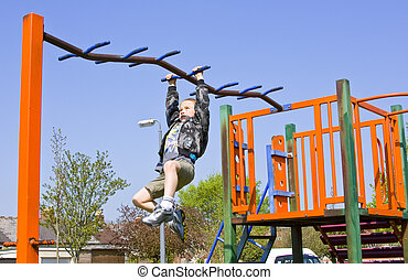Young six year old boy plays on the equipment in a children's pl