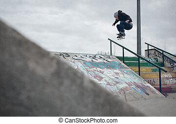 Skateboarder doing a Ollie over the rail in a skatepark - ...
