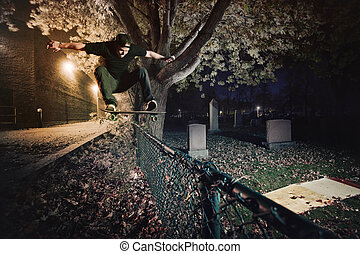 Skateboarder doing a Ollie trick over a Fence at night -...