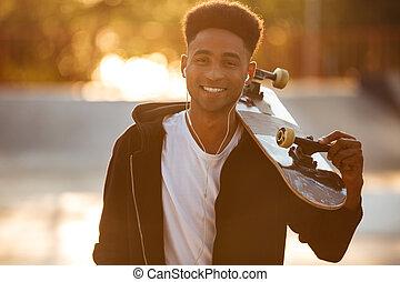 Young skateboarder man holding skateboard