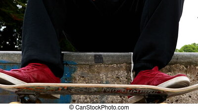 Young skateboarder sitting