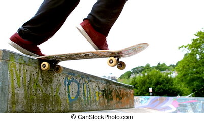 Young skateboarder skating the outdoor skatepark in slow...