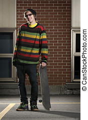 Young skateboarder standing holding his board