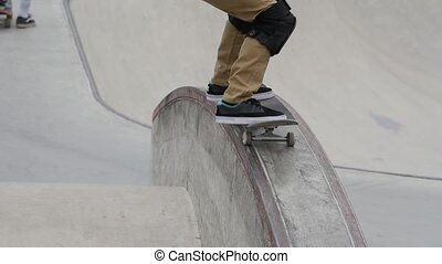 Young skater in knee-caps jumping on a ledge in a skate park