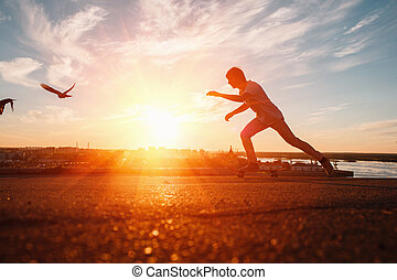 Young skaters training in the park in sunset. Birds.