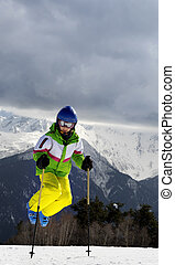 Young skier jump with ski poles in sun winter mountains