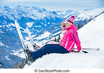 Young girl with her mother in a ski outfit sitting on the snowy hill in the Zillertal Arena, Austria