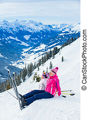 Young girl with her mother in a ski outfit sitting on the snowy hill in the Zillertal Arena, Austria. Vertical view