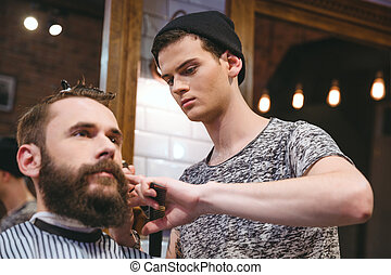 Young skillful barber making haircut to handsome bearded man