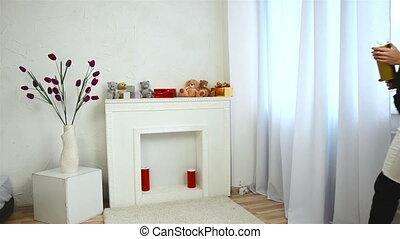 skinny women coming to white fireplace with toys puts a candle