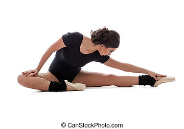 Young slender ballerina doing stretching in studio