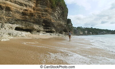 Young slender brunette is walking along the seashore and looking at the sea. Beautiful fashion model is posing on the Balinese beach near the rock strolling in the water.