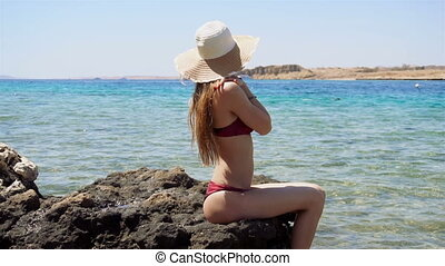 young slender girl in a bathing suit and hat sits sideways on a rock and looks at the ocean