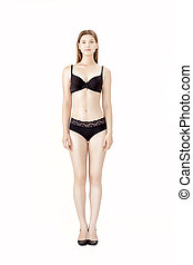 Young slender woman in black lingerie isolated on white background
