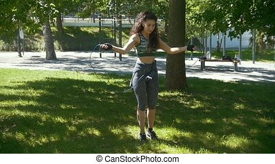 Young slender woman jumping with a rope, boxing workout outdoors at sunny day
