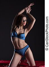 Young slender woman posing in blue lingerie