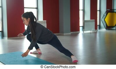 Young slender woman stretching her legs in red fitness room,...