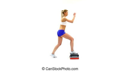 Young slender woman training on stepper
