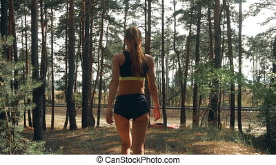 young slim athletic girl in short shorts with sexy buttocks walks through the Woods