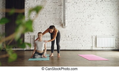 Young slim blonde is learning king pigeon pose from friendly...