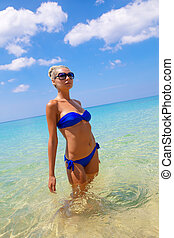 Young slim blonde swimming in the sea