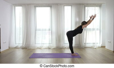 Young slim blonde woman practicing and teaching yoga exercises in studio