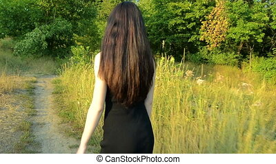 young slim brunette with thick hair goes on green field on a sunny day in a black dress