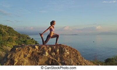 Young Slim Concentrated Girl Does Asanas on Large Stone
