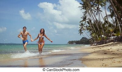 Young slim couple holding hands running on tropical beach by...