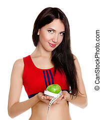 Young slim girl holding an apple with a measuring tape