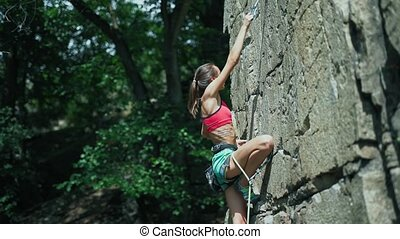 young slim muscular woman rockclimber climbing on tough sport route, hunging on carabiner and trying to attach the rope to quickdraw. outdoors rock climbing and active lifestyle, slow motion dangerous climbing details