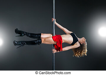 Young slim pole dance woman exercising over dark